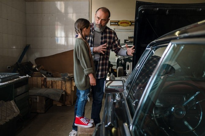 Father showing daughter his garage workshop